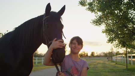 kleštěnec : SLOW MOTION, CLOSE UP: Cheerful cute little girl embracing and caressing beloved powerful dark bay gelding at magical sunset. Happy kid hugging and cuddling strong stallion on countryside horse ranch