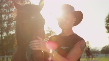 mocný : SLOW MOTION, CLOSE UP: Happy smiling cowboy caressing big mighty dark brown horse on magical sunny summer day. Cheerful senior man cuddling beautiful strong stallion on vast countryside ranch farm