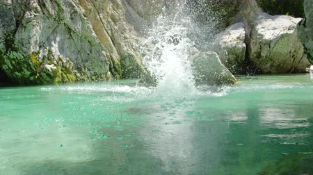 rapids : SLOW MOTION CLOSE UP: Happy young man jumping headfirst into water off a big rock in the middle of freezing cold and beautiful green Soca river. Cheerful guy diving into refreshing riverbed head first Stock Footage