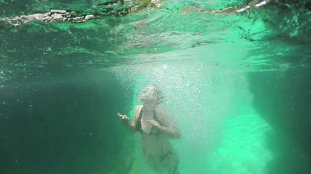 slovinsko : SLOW MOTION CLOSE UP UNDERWATER: Cheerful young woman jumping off a high cliff into crystal clear emerald Soca river. Adventurous girl surrounded by many bubbles swimming to the surface for air