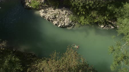 skalní útes : AERIAL: Caucasian woman swimming frog style along rocky riverbank in beautiful green river in the middle of lush overgrown forest. Relaxing summer holiday in deep wild cliffy gorge on amazing day