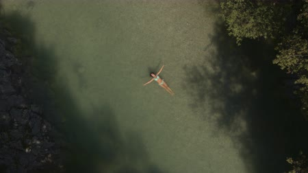 starfish : AERIAL, CLOSE UP, DISTANCING: Flying close above pretty Caucasian girl in bikini flowing and relaxing on water surface in stunning magical wild emerald river in the middle of lush deciduous forest Stock Footage