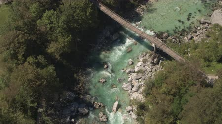 curso : AERIAL: Flying above big beautiful wooden rope bridge leading over stunning emerald mountain river stream. Clear raging whitewater rapids running fast between big sharp rocks in rocky riverbed Vídeos