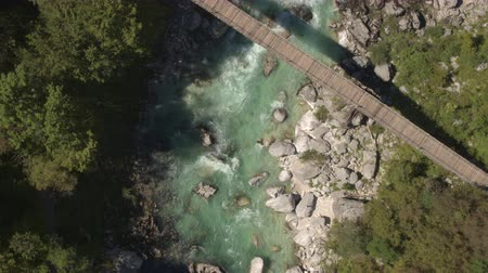suyolu : AERIAL: Flying above big beautiful wooden rope bridge leading over stunning emerald mountain river stream. Clear raging whitewater rapids running fast between big sharp rocks in rocky riverbed Stok Video