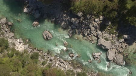 slovenya : AERIAL: Flying above amazingly fast current in rocky riverbed, furious white water running between sharp rocks. Beautiful wild river flowing through stunning landscape surrounded by lush forest Stok Video