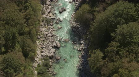 猛烈な : AERIAL: Flying above amazingly fast current in rocky riverbed, furious white water running between sharp rocks. Beautiful wild river flowing through stunning landscape surrounded by lush forest 動画素材
