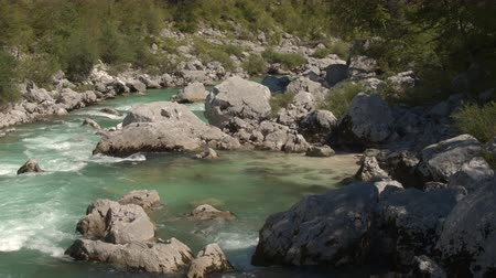 suyolu : AERIAL CLOSE UP: Flying close above amazingly fast current of crystal clear Soca river flowing in rocky riverbed. Furious white water running between big sharp rocks in beautiful wild landscape Stok Video
