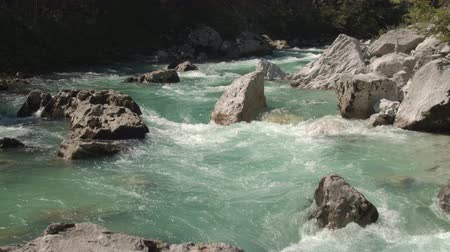 猛烈な : AERIAL CLOSE UP: Flying close above amazingly fast current of crystal clear Soca river flowing in rocky riverbed. Furious white water running between big sharp rocks in beautiful and wild landscape 動画素材