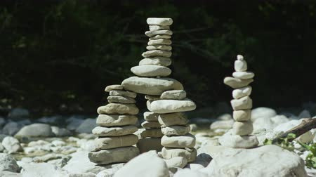 babona : CLOSE UP, SLOW MOTION: Amazing stone sculptures made by tourists visiting Slovenia laying on rocky riverbank to mark hiking trail. Natural gemstones used in meditation connecting body, soul and mind