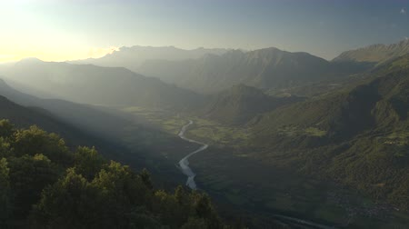 ziguezague : AERIAL: Flying above beautiful river meandering through green mountain valley in sunny misty summer morning. Amazing vast and lush forest covering slope foothills of tall overgrown mountains and hills Stock Footage