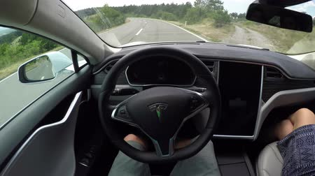 itself : CRNI KAL, SLOVENIA - JULY 20, 2016: Self driving electric car using sensors and navigating without driver on coastal road. Unrecognizable person steering autonomous car fast with no hands on wheel