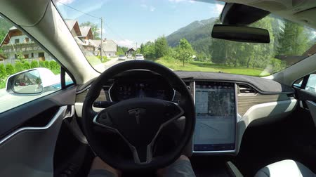 itself : KRANJSKA GORA, SLOVENIA - JULY 17 2016: Unrecognizable person self driving autonomous electric car, navigating and steering without driver on countryside road. Vehicles coming on the opposite side