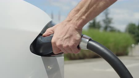 economical : CLOSE UP, SLOW MOTION: Man plugging in electric car at super charging station. Luxury white electrical car recharging. Environmentally conscious man charging his electric vehicle Stock Footage