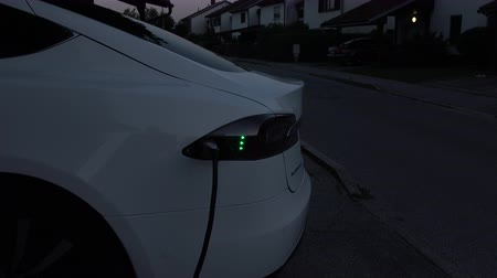 tankowanie : CLOSE UP: Luxury electric car charging battery cells at home in the yard. Expensive white electrical car recharging. Environmentally conscious transportation vehicle plugged in, refilling