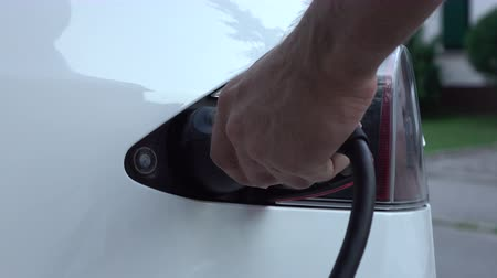 unplug : CLOSE UP: Unrecognizable man disconnecting electric car from charging station when batteries full. Luxury white electrical Tesla car power recharged. Unplugging the cable when battery filling complete Stock Footage
