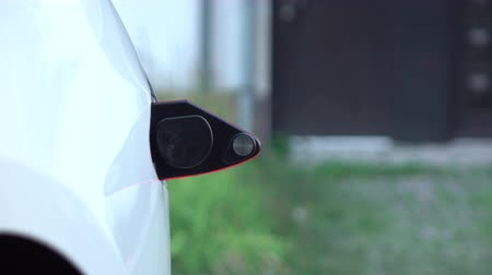 unplug : CLOSE UP: Man disconnecting electric vehicle from charging station when batteries full and shutting the charge port. Unplugging the cable from car when battery filling complete, power recharged