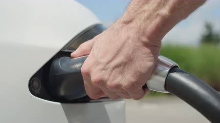 unplug : CLOSE UP, SLOW MOTION: Unrecognizable businessman unplugging electric car from charging station. Luxury white electrical Tesla car full. Disconnecting the cable when electrical power filling compete