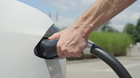 economical : CLOSE UP, SLOW MOTION: Unrecognizable businessman unplugging electric car from charging station. Luxury white electrical Tesla car full. Disconnecting the cable when electrical power filling compete