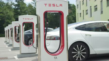 tesla motors : LJUBLJANA, SLOVENIA - JULY 10 2016: White and black Tesla autonomous electric cars refilling energy at free of charge super fast charging station on parking lot. Luxury vehicles charging battery