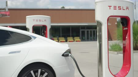 tesla motors : LJUBLJANA, SLOVENIA - JULY 10 2016: White Tesla autonomous electric cars filling energy at Supercharger charging station. New age technology luxury vehicle recharging rechargeable batteries