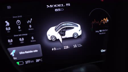 tesla model s : LJUBLJANA, SLOVENIA - JULY 10: Innovative instrument technology in Tesla Model S. Dashboard display showing charging batteries status, average consumption, voltage and navigation map while plugged in Stock Footage