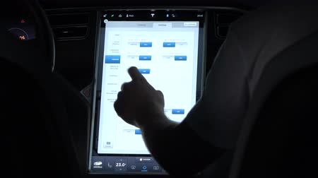 tesla model s : LJUBLJANA, SLOVENIA - JULY 10 2016: passenger going through settings on computer display in Tesla Model S electric car. Innovative software technology enables the driver driving comfortably