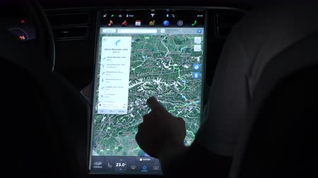 economical : LJUBLJANA, SLOVENIA - JULY 10 2016: Unrecognizable man moving through map, zooming it out and monitoring consumption statistics on innovative touchscreen computer display in Tesla Model S electric car
