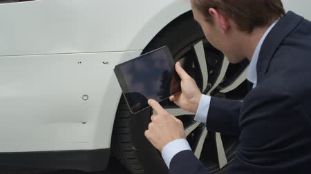 dent : CLOSE UP, SLOW MOTION: Insurance inspector evaluating estimated damage with digital tablet. Agent calculating and assessing damages of scratches on car fender and doesnt approve the claim to pay Stock Footage