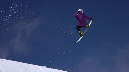 snowboarder : SLOW MOTION: Young pro snowboarder riding the half pipe in big mountain snow park, jumping high out of the halfpipe wall, performing tricks and rotations with grabs in sunny winter Stock Footage