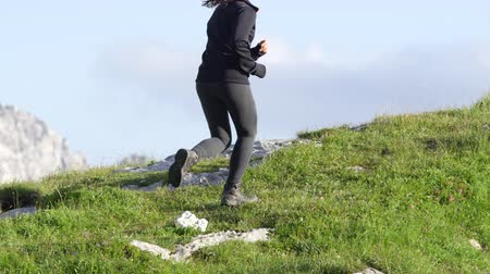 salita : SLOW MOTION CLOSE UP: Powerful young female running uphill in mountains on beautiful hiking path with rocks and meadow on sunny summer day. Smiling active girl trekking and jogging on rocky ridge