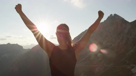 alpinismo : SLOW MOTION, CLOSE UP: Young female standing on the edge of the cliff and raising her hands up against high rocky mountains sunbathing in evening sun. Happy girl enjoying success and stunning view Archivo de Video