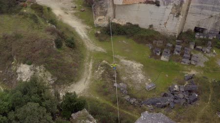 такелаж : AERIAL: Flying around extreme highliner walking long highline tensioned between rock formations in aggregate quarry. Active guy balancing and slacklining with backup on strong webbing over deep pit Стоковые видеозаписи