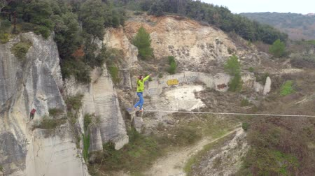 cordame : AERIAL, CLOSE UP: Flying above extreme highliner walking long highline tensioned between rocky walls in abandoned quarry. Young guy slacklining with safety harness, loosing his balance and falling