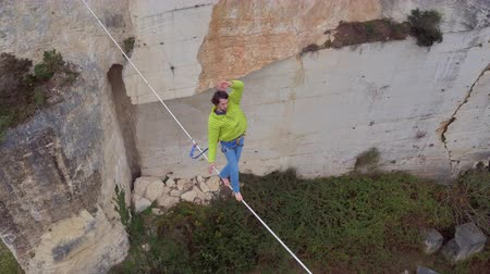 slacklining : AERIAL, CLOSE UP: Flying above extreme highliner walking highline tensioned between walls in abandoned rock quarry. Man with safety harness on slacking and balancing on bouncy slackline over canyon