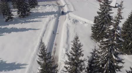 lodge : AERIAL: Turquoise sport car driving on slippery frosty street past traditional alpine chalet in dreamy ski resort. Picturesque mountain valley and vast conifer forest on beautiful sunny winter day