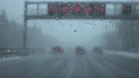 závěj : POV, CLOSE UP: Cars speeding on dangerous multilane highway with poor visibility on dark foggy and rainy winter day in bad weather. Wet snow falling on slippery road making worse condition for driving