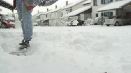 čištěný : SLOW MOTION CLOSE UP DOF: Shoveling manually white snow from the street with shovel and clearing frozen path. Winter job and removal of deep snowy blanket, digging, scooping, throwing it on the road Dostupné videozáznamy