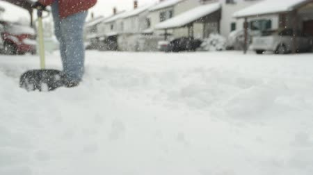 tisztított : SLOW MOTION, CLOSE UP: Shoveling manually fresh white snow from the street with shovel and clearing frozen path. Winter job and removal of deep snowy blanket, digging, scooping, throwing it on the road Stock mozgókép