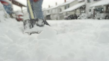 tisztított : SLOW MOTION CLOSE UP DOF: Shoveling manually white snow from the street with shovel and clearing frozen path. Winter job and removal of deep snowy blanket, digging, scooping, throwing it on the road Stock mozgókép