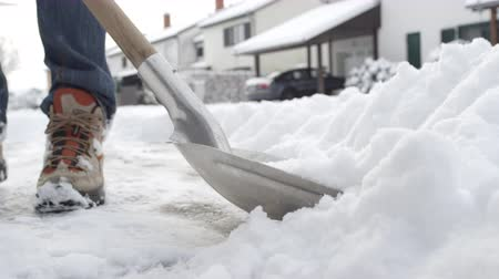 radura : SLOW MOTION, CLOSE UP, DOF: Shoveling manually white snow from the street with shovel and clearing frozen path. Winter job and removal of deep snowy blanket, digging, scooping, throwing it on the road
