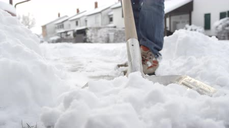 čištěný : SLOW MOTION, CLOSE UP, DOF: Guy shoveling manually white snow from the street with shovel, clearing frozen path. Winter job and removal of deep snowy blanket, digging, scooping, throwing it on pile