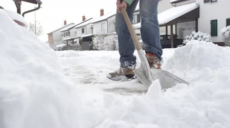 tisztított : SLOW MOTION, CLOSE UP, DOF: Guy shoveling manually white snow from the street with shovel, clearing frozen path. Winter job and removal of deep snowy blanket, digging, scooping, throwing it on pile