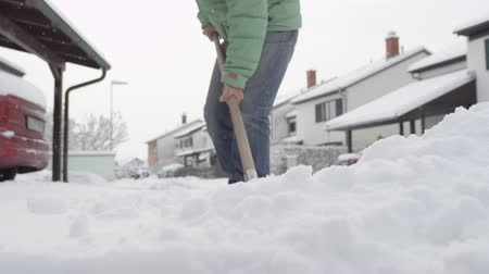 čištěný : SLOW MOTION, CLOSE UP, DOF: Guys shoveling manually white snow from the street with shovel, clearing frozen road. Winter job and removal of deep snowy blanket, digging, scooping, throwing it on pile
