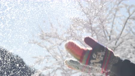 knitted gloves : SLOW MOTION CLOSE UP DOF: Unrecognizable woman in warm knitted colorful gloves throwing snowflakes in the air. In the backgrounds green conifer forest, mountains and bare tree crown covered with snow