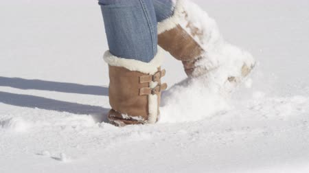 stepping : SLOW MOTION CLOSE UP: Unrecognizable female in jeans and warm winter boots walking in smooth deep snow blanket. Woman in sheepskin boots wading through fresh snow on a beautiful sunny Christmas day
