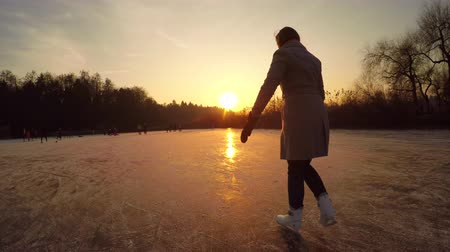 paten yapma : CLOSE UP: Female recreational ice skater iceskating fast in natural rink on frozen lake at magical sunset on Christmas eve. People enjoying holidays and playing hockey with kids and friends in nature Stok Video