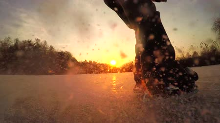 spraying : SLOW MOTION, CLOSE UP, LOW ANGLE VIEW: Extreme male ice skater spraying snow when making ice hockey stop on natural frozen lake at beautiful golden sunset on cold winter day before Christmas evening