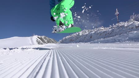 extreme close up : SLOW MOTION CLOSE UP: Extreme snowboarder jumping ollie on perfectly groomed snow in sunny mountain ski resort. Snowboarder having fun snowboarding and jumping, splashing snow in snowy mountain