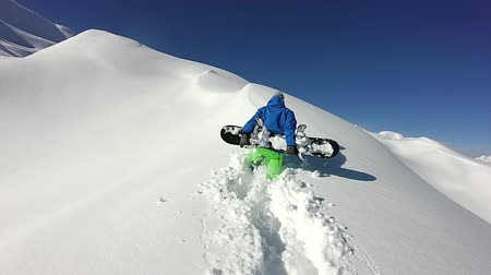spraying : CLOSE UP: Extreme snowboarder hiking uphill in fresh powder snow on a snowy mountain slope in winter. Freeride snowboarder climbing to the mountaintop in powder snow backcountry in mountain ski resort Stock Footage
