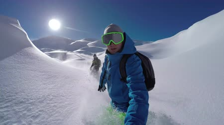 freeride : SELFIE: Cheerful snowboarders having fun snowboarding backcountry on sunny winter day in snowy mountains. Extreme freeride snowboarders riding fresh powder snow and doing powder turns off piste